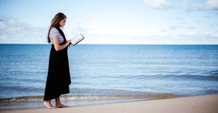 37231-womanreadingBibleonBeach-Bible-Beach-Unsplash.1200w.tn